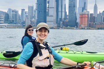 two smiling women in sea kayaks in front of the Hudson Yards on the Hudson River in NYC