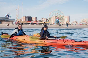 a smiling man and woman sitting in an orange double sea kayak in front of Coney Island Beach