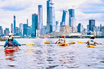 3 kayakers on the Hudson River looking at the Hudson Yards skyline