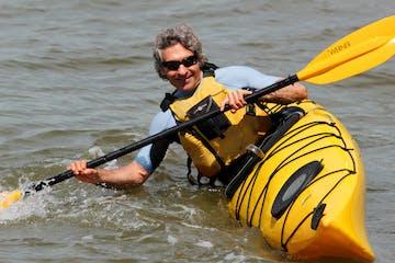 A man tilting a sea kayak show how to do kayak edging and bracing strokes