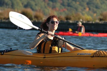 two people riding sea kayaks on the water in the autumn