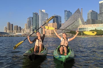 two women on green sit on top kayaks in front of the VIA Building in Manhattan
