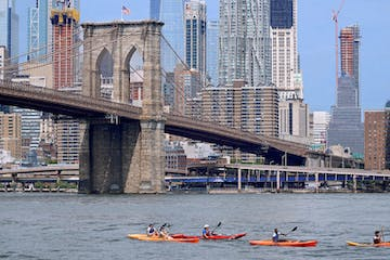 five kayakers on the East River near the Brooklyn Bridge
