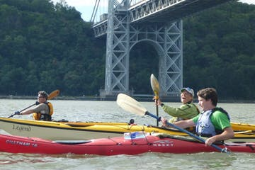 a woman and two men riding sea kayaks on the Hudson River under the George Washington Bridge