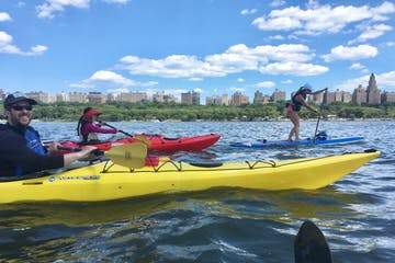 two people on sea kayaks and one woman on a stand up paddle board on the Hudson River near Manhattan's Upper West Side