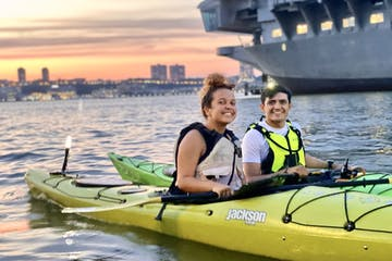 a man and a woman in sea kayaks in the water during sunset