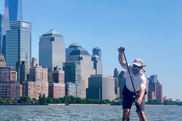 a man riding a stand up paddle board on the Hudson River with the Freedom Tower and the Financial District of Manhattan in the background