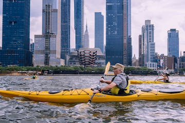 two men and a woman riding sea kayaks in front of the Hudson Yards on the Hudson River in NYC