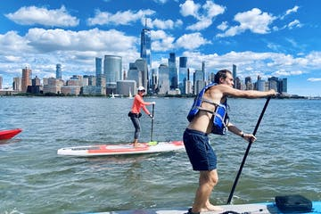 a man and a woman riding stand up paddle boards at the Hudson River and the Battery in NYC