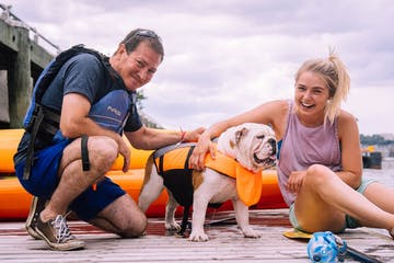 a man and woman with a bulldog wearing a life jacket on the kayak dock at Pier 84 Boathouse in Manhattan