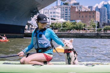 a woman on a stand up paddle board with her dog in front of the Intrepid Aircraft Carrier in Midtown Manhattan