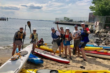 a group of people standing next to kayaks and paddle boards at the beach
