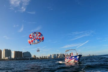 a group of people flying kites in a body of water