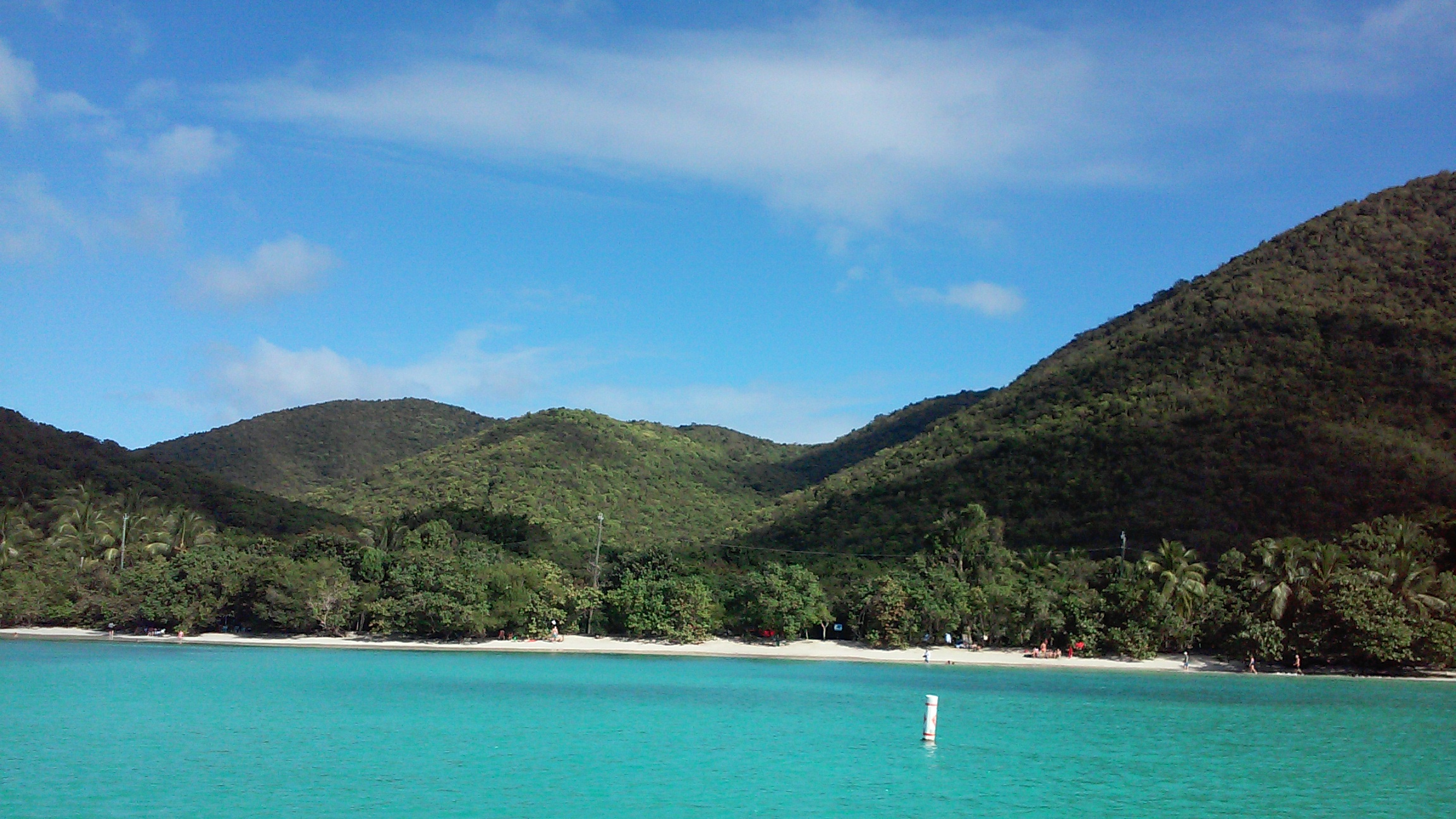 St. John has white sandy beaches lined with palm trees and rimmed with green hills, this photo shows Caneel Bay and Hawksnest Bay