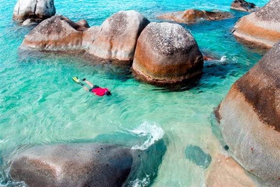 This girl is walking through the boulders at the Baths in Virgin Gorda in the sunlight and through the aqua water