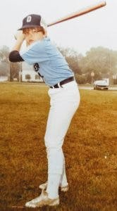 a baseball player holding a bat while standing next to home plate