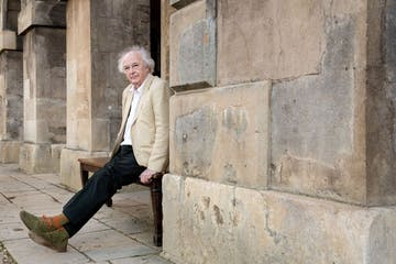Philip Pullman sitting on a ledge talking on a cell phone