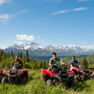 Group sitting on ATVs in front of an Alaskan Mountain Range