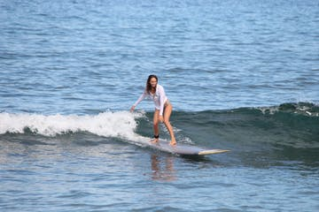 a girl riding a wave on a surfboard in the water