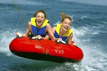 two girls riding a tube on the water