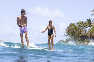 a man and a woman riding a wave on a surfboard in the water