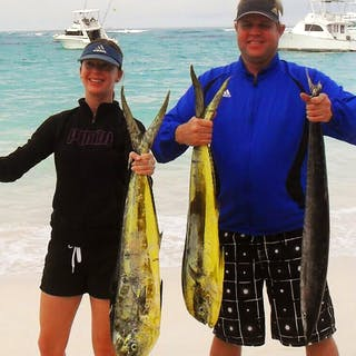 A couple holding their day's catch from a Punta Cana fishing charter