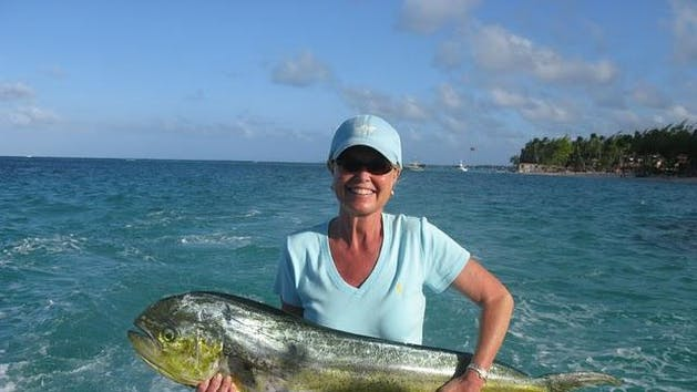 Woman holding a fish caught in Punta Cana