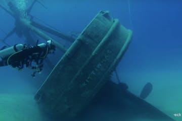 a deep shipwreck explore by a scuba diver