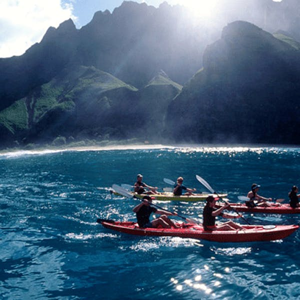 a group of people sea kayaking napali coast