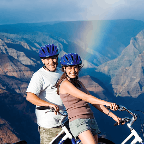 couple on bike with waimea canyon and rainbow in background