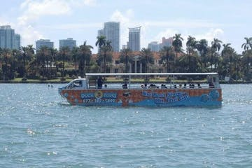 a small boat in a body of water with a city in the background