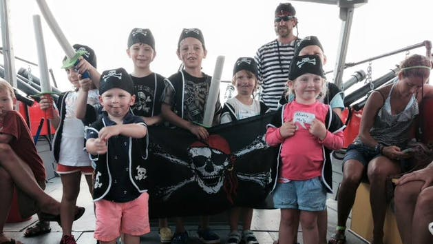 Group of kids posing with pirate costumes on.