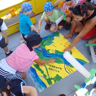 Kids pointing to a treasure map