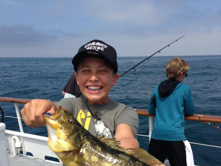 young smiling boy holding fish