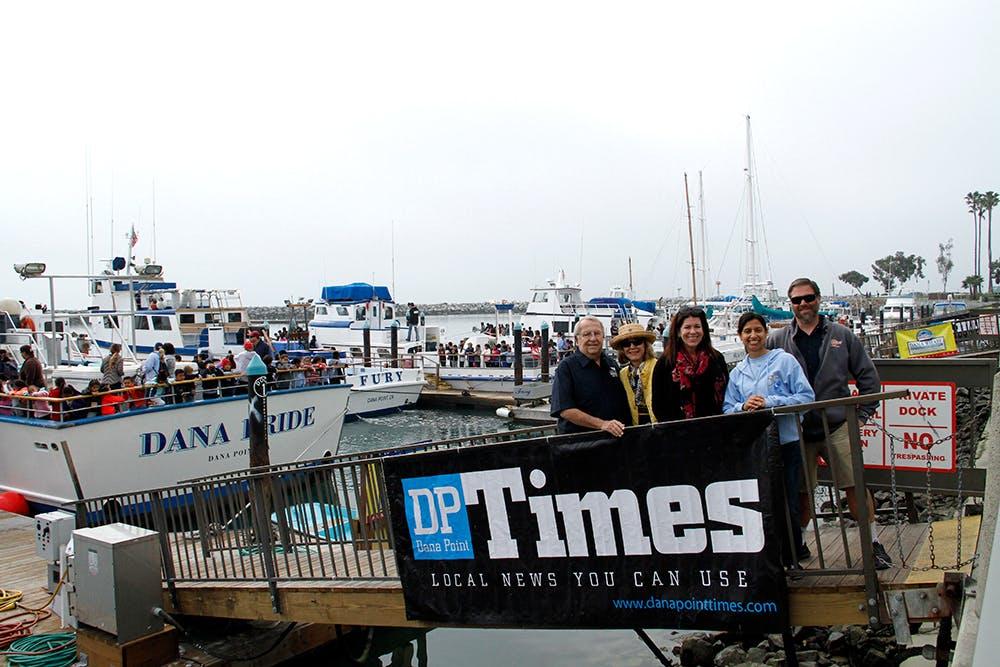 5 people standing on dock near Dana Pride