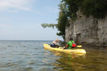 A couple on a tandem kayak on the death's door bluff tour