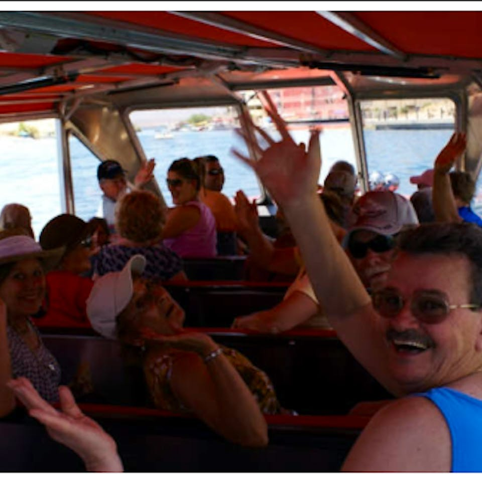 People waving at the camera while riding on the jet boat