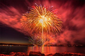 fireworks in the sky over a body of water