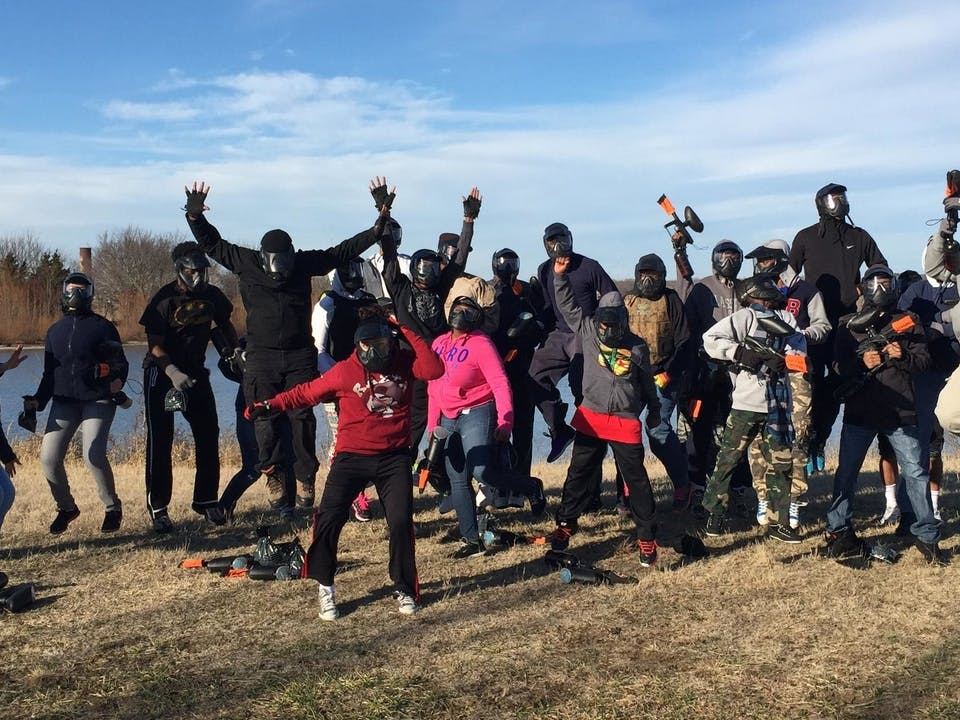 a group jumping with paintball guns