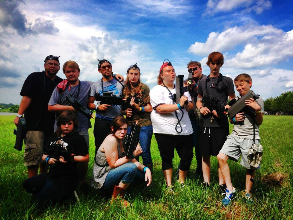 a group of you individuals posing with laser tag guns