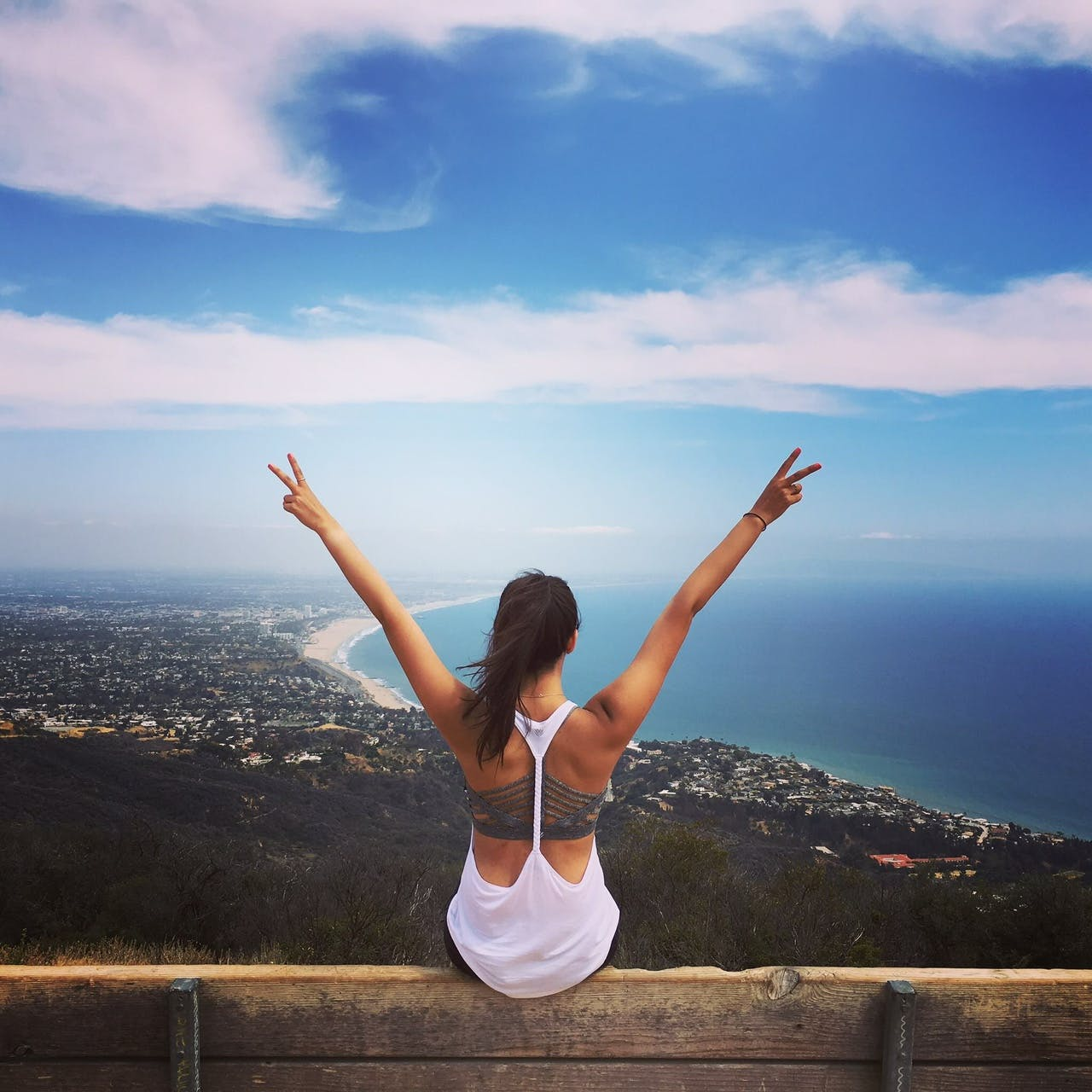 A girl holding up two peace signs while sitting on the edge of a bench overlooking the coast