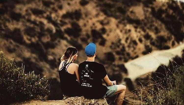 A couple sits looking at Los Angeles from the Runyon Canyon Trail in West Hollywood, California