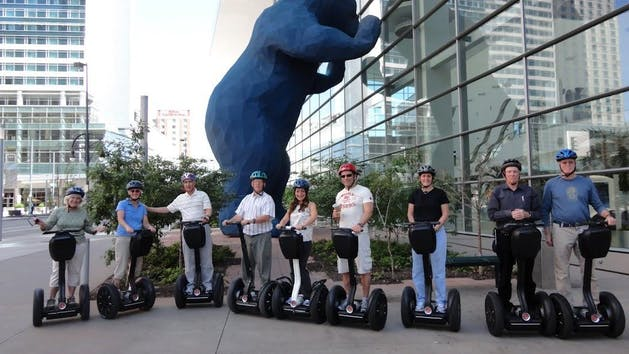 group of people on segways in front of the blue bear in downtown denver