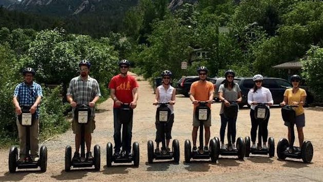 a group of people on Segways in front of some lush greenery
