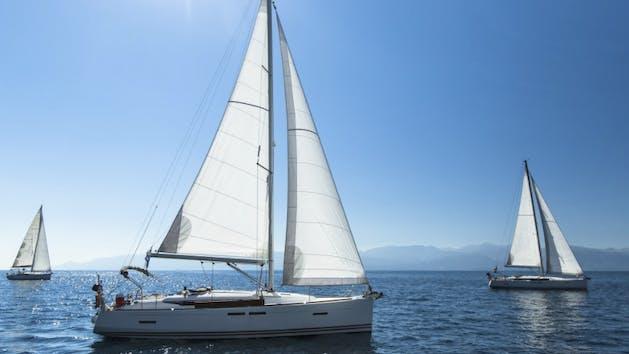 three sailboats on the ocean
