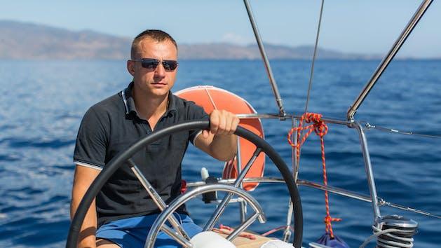 man sitting at steering wheel of boat