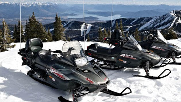 three snowmobiles out on the ridge