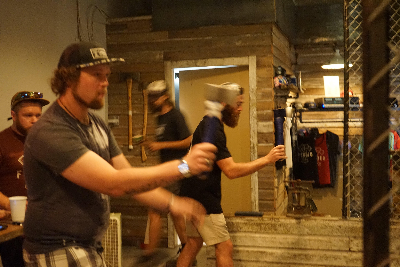 Men throwing axes indoors