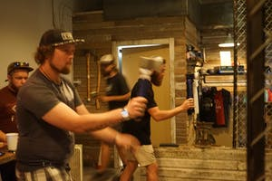 Men throwing axes indoors