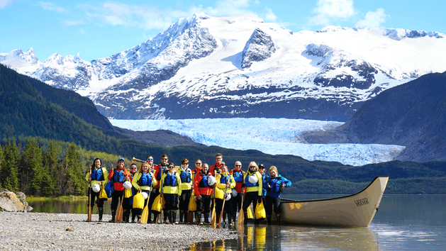 A group smiling standing next to Mendenhall Lake with Mendenhall Glacier in the background.
